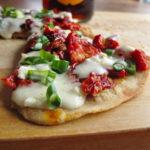 Piece of skillet pizza with dried tomatoes and a beer crust