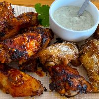 Plate of harissa baked wings and smoked wings with parmesan topping