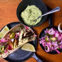 Fish tacos with avocado cream and pickled onions